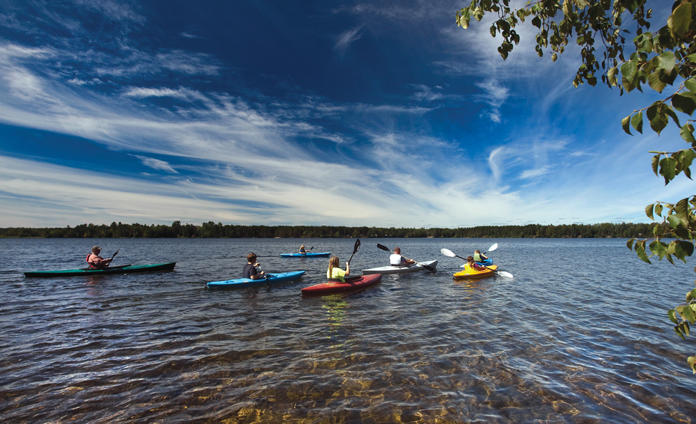 Kayakers paddle the clear waters of Alcona Pond