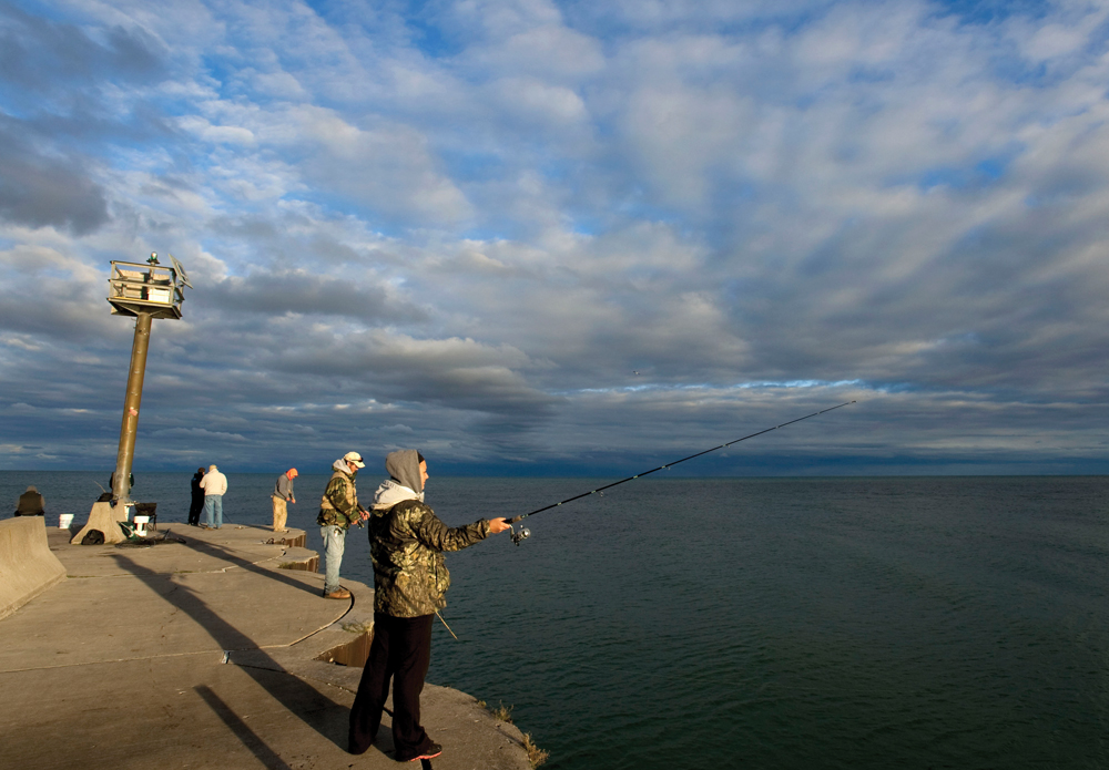 anglers try their luck off the Oscoda pier at sunrise