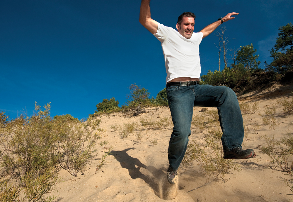 Joe Roman of Royal Oak bounds down a massive sand dune at Cooke Pond
