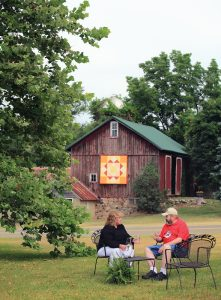 """Chuck and Deb Peterson with their quilt """"Around the Corner"""" on East Z. Ave."""