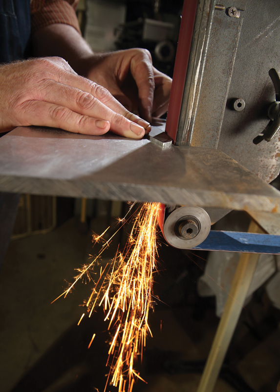 Bob Braendle grinds a steel blade into shape.