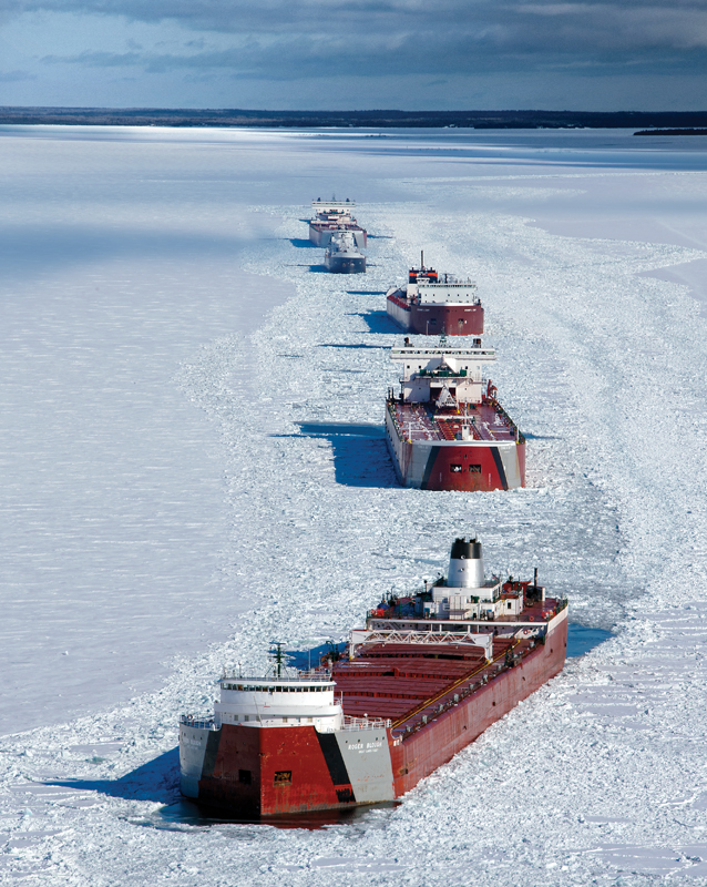 """A convoy of """"lakers"""" wait for an icebreaker escort in the St. Mary's River."""
