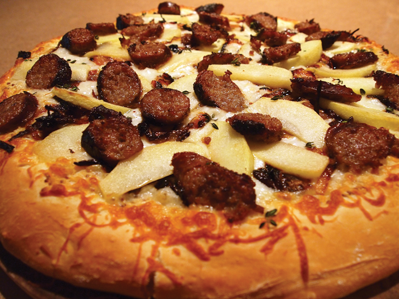 Celebrate at home with this Bavarian-inspired pizza featuring Arcadia Brewing Company's Jaw Jacker with brats, mustard, caramelized onions and apples
