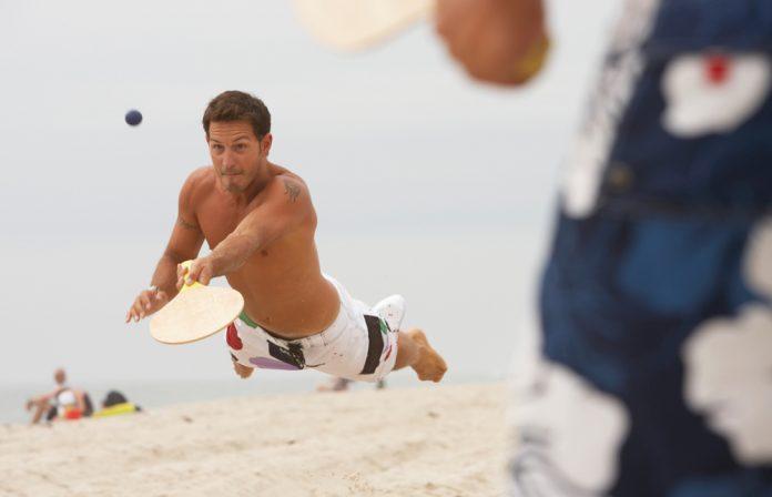 man playing paddle ball on beach