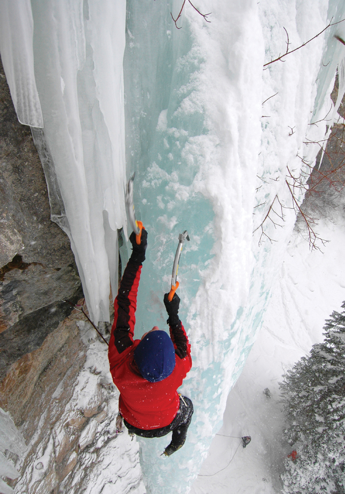 Ice Climber Extreme Adventurer on Steep Frozen Waterfall