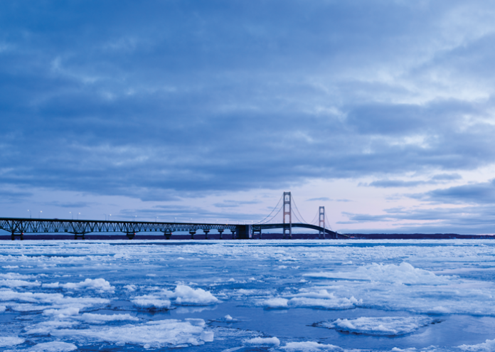 A bridge during sunrise over an ice covered lake.